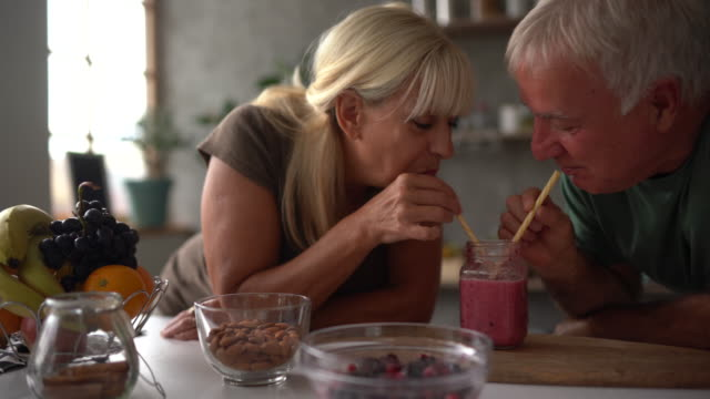Lovely senior couple drinking freshly made smoothie at home