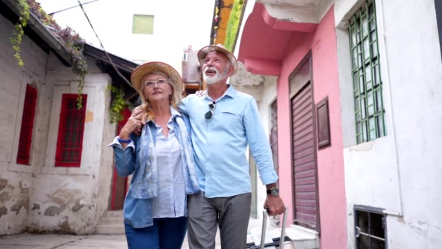 可愛的老夫婦走過一條城市街道, 環顧四周 - 旅遊業 個影片檔及 b 捲影像