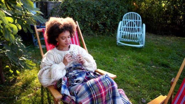 Lovely serene woman drinking tea outdoors