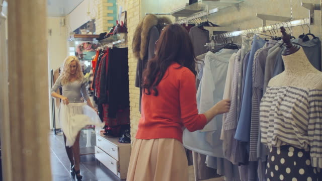 Lovely Shoppers Beautiful blonde girl enjoying shopping with her friend: she trying on tulle skirt, dancing and laughing in fashion boutique tulle netting stock videos & royalty-free footage