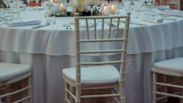 vídeos de stock, filmes e b-roll de cadeiras brancas encantadoras atrás da tabela redonda que é toda decorada no branco - fine dining