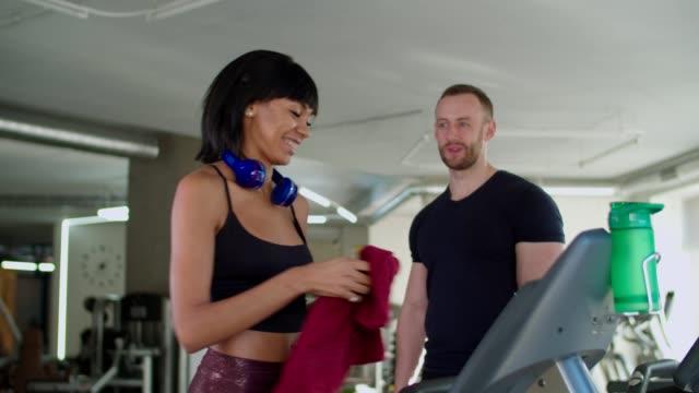 härlig kvinna efter behandling cardio workout på löpbandet - black woman towel workout bildbanksvideor och videomaterial från bakom kulisserna