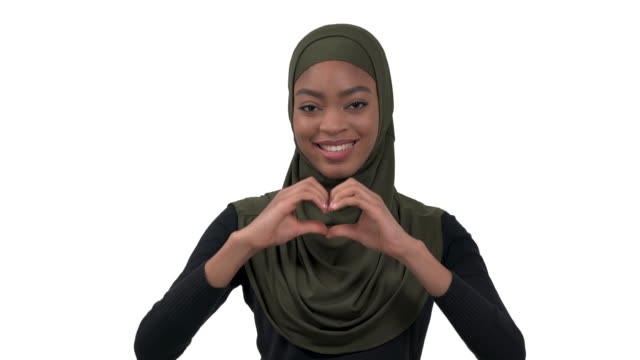 Lovely woman in hijab with charming smile holding hands in heart shape showing her love and sympathy. Body language concept. Isolated, on white background