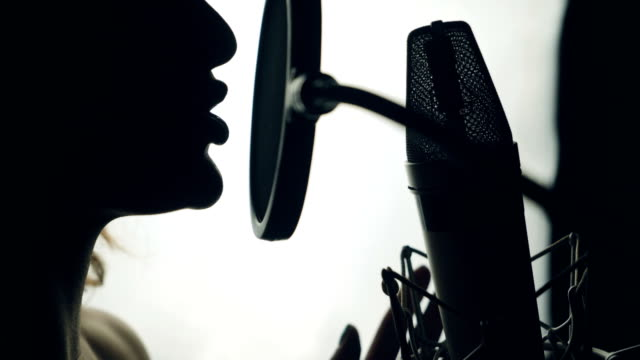 Lovely woman singing into the microphone in the recording studio.