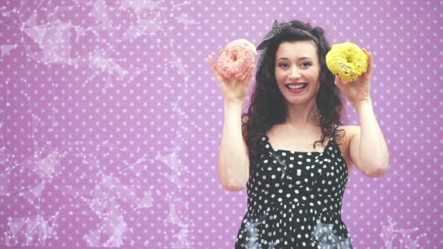 lovely young curly girl hiding her eyes behind two yummy doughnuts in pink and yellow icing, grinning happily. - paczka sukienka filmów i materiałów b-roll