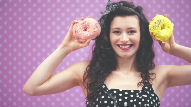 lovely young curly girl standing, raising up two yummy doughnuts in pink and yellow icing to the level of her ears. - paczka sukienka filmów i materiałów b-roll