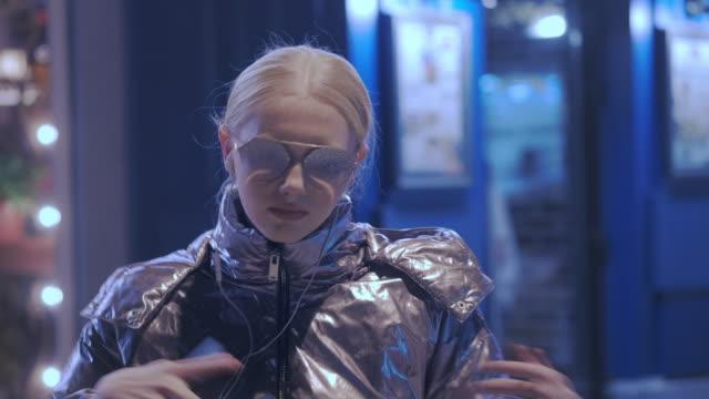 härlig ung flicka dansar på natten på gatan. klädd i en glänsande jacka och solglasögon. håller en smartphone i handen, växlar låten - street dance bildbanksvideor och videomaterial från bakom kulisserna