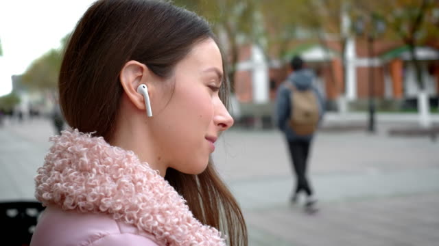 lovely young girl is listening to music through wireless white headphones. sits on a bench in the street in the fall. holds a smartphone in his hand, switches the song - cuffie wireless video stock e b–roll
