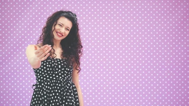 Lovely young girl with kinky hair, in black polka-dots dress dancing, waving her hands, calling to join her, pointing at copy space for text or product.