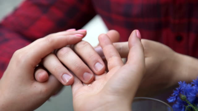 lovers holding each other's hands in kafe - young couple wedding friends video stock e b–roll