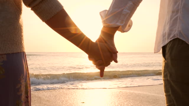 Lovers holding hands at the beach.