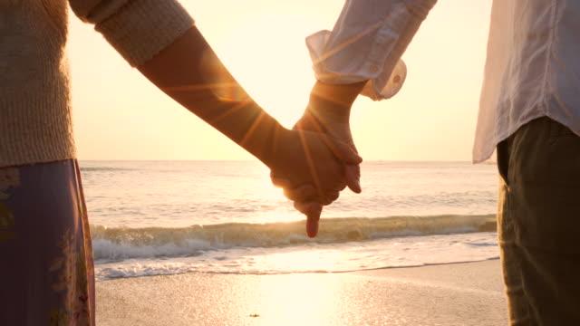 vídeos de stock, filmes e b-roll de amantes de mãos dadas na praia. - mão humana