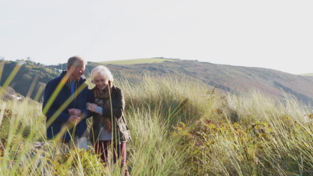 Loving Active Senior Couple Walking Arm In Arm Through Countryside Together video
