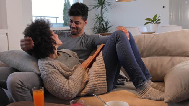 stockvideo's en b-roll-footage met liefdevolle afrikaanse amerikaanse echtpaar een boek te lezen terwijl u ontspant op de bank thuis. - couch