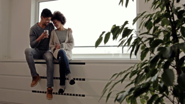Loving African American couple talking while relaxing by the window during coffee time. video