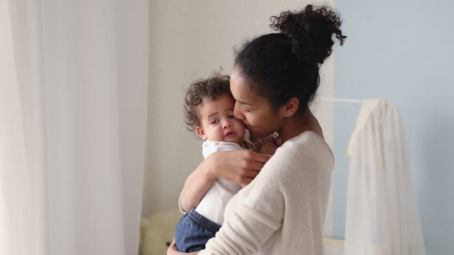 vídeos y material grabado en eventos de stock de amante madre africana sosteniendo linda hija bebé besando niño pequeño - madre
