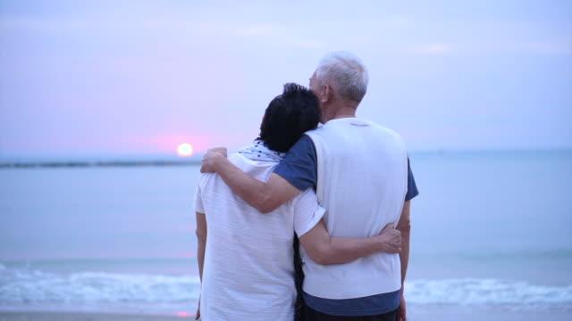 愛するアジア シニア カップルの海の日の出で一緒に幸せです - アジア旅行点の映像素材/bロール
