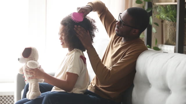 loving black father doing brushing afro hair of kid daughter - córka filmów i materiałów b-roll