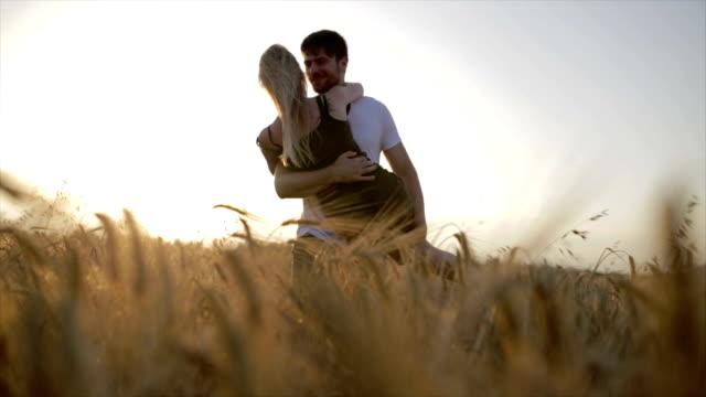 恩愛的夫妻,一個男人親吻一個漂亮的年輕女人和她抬起頭和與她共舞,場上在日出或日落時 - {{asset.href}} 個影片檔及 b 捲影像