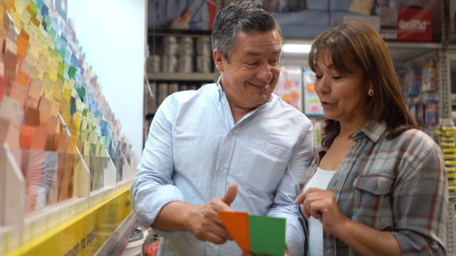 loving couple at home improvement choosing a color to paint their house and holding a palette - tavolozza video stock e b–roll