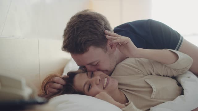 Loving Couple awaking A couple awaking at morning in their bed. Its a beautiful summer day outside. young couple stock videos & royalty-free footage