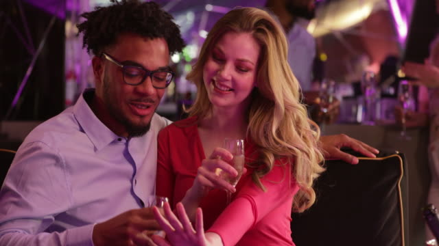 Loving Couple Enjoying a Drink Surface level view of a loving couple sitting in a club enjoying time together. The couple are leaning into each other and having a glass of champagne. falling in love stock videos & royalty-free footage