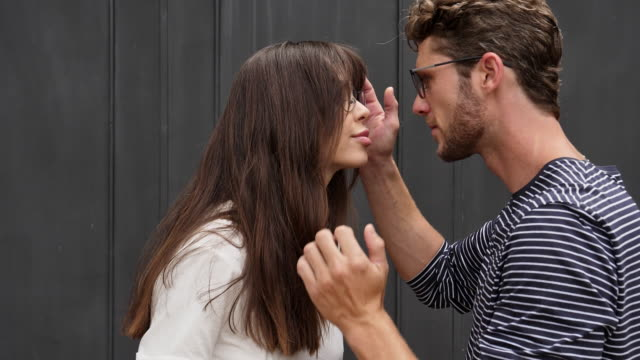 loving couple face to face - brunette woman eyeglasses kiss man video stock e b–roll