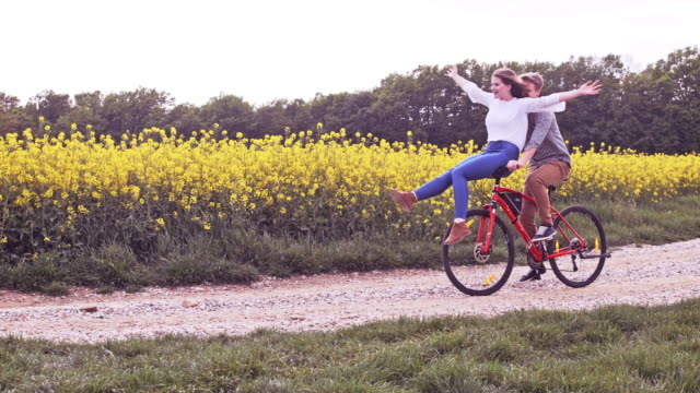 SLO MO Loving couple having fun riding on the handlebars Slow motion shot of a loving woman sitting on boyfriends bicycle handlebars as they cycling on a dirt road along canola fields in the countryside. Slovenia handlebar stock videos & royalty-free footage