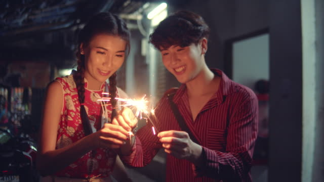Loving Couple Holding sparklers Young chinese couple holding a sparkler somewhere in the city at night. Bangkok, Thailand. chinese new year stock videos & royalty-free footage