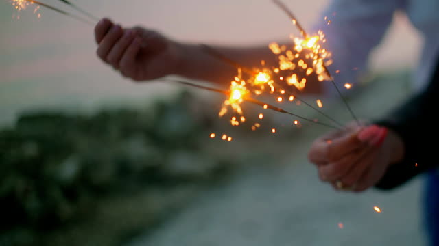 loving couple holding sparklers - beach fashion stock videos and b-roll footage