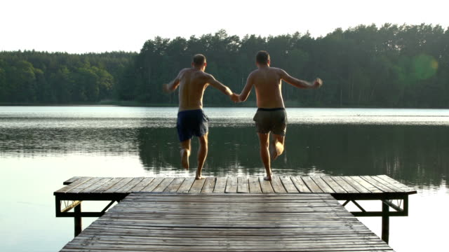 Loving couple jumping into lake Summer activities. Couple jumping into lake young couple stock videos & royalty-free footage