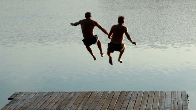 Loving couple jumping into lake Summer activities. Couple jumping into lake gay man stock videos & royalty-free footage