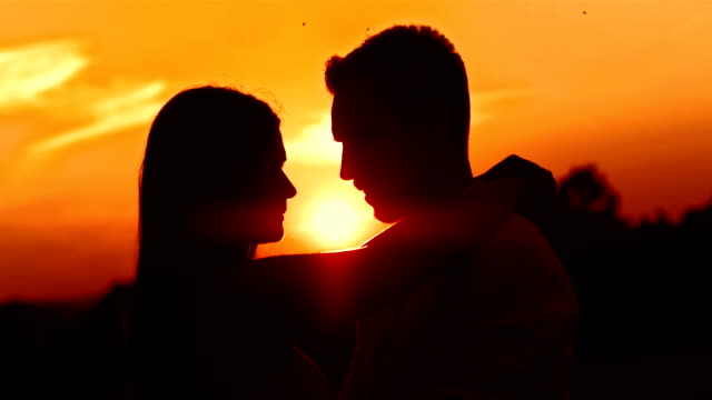 HD: Loving Couple Kissing At Sunset HD1080p: Silhouette of a couple in embrace kissing outdoors at sunset. falling in love stock videos & royalty-free footage