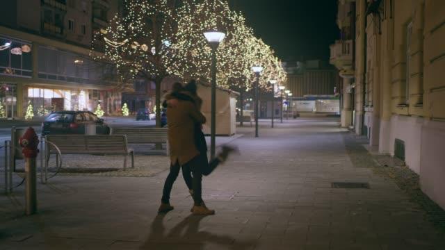 クリスマスの装飾で飾られた ds 愛情のあるカップルは、路上でのキス - 十二月点の映像素材/bロール