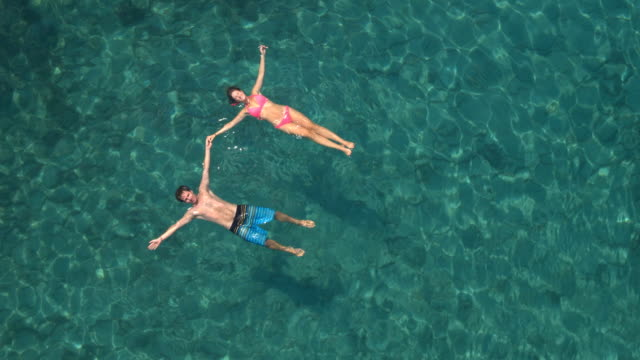 AERIAL: Loving couple on dreamy holidays swimming starfish float holding hands video