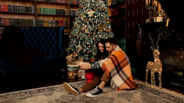 A loving couple opens presents at a Christmas tree video