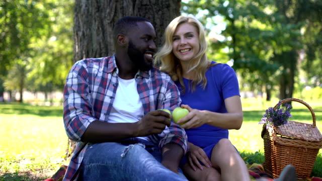 kochająca para pokazująca zielone jabłka w aparacie, wybierając zdrowe produkty - happy holidays filmów i materiałów b-roll