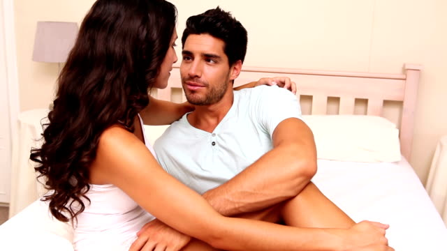 Loving couple sitting on bed together video