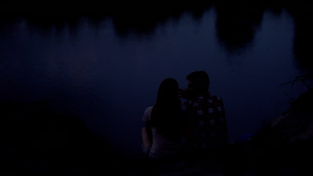 vídeos de stock e filmes b-roll de loving couple sitting on river bank, embracing and talking, admiring scape, date - man admires forest