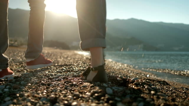 Loving couple strolling along stony beach on sunny day video
