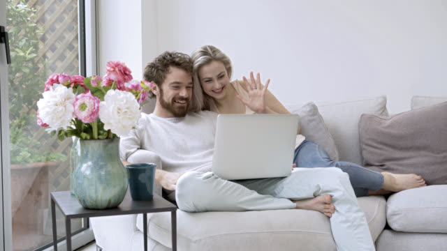 Loving couple video chatting with someone on their laptop video