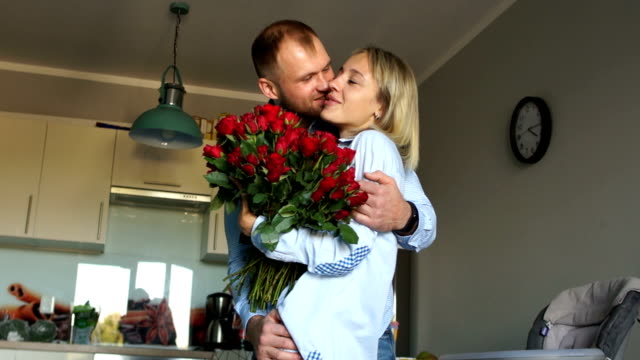 Loving couple with a bouquet of flowers in the kitchen. Newlyweds on Valentine's Day cuddle at home