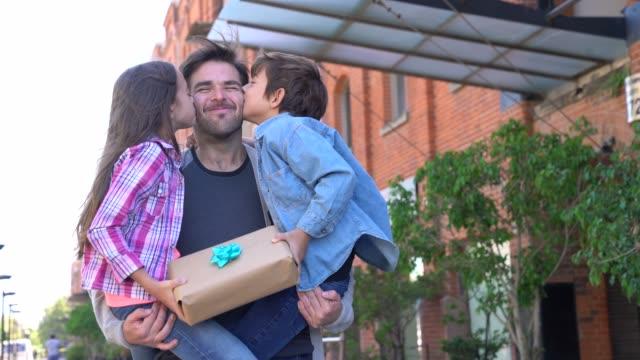 vídeos de stock, filmes e b-roll de pai loving que carreg seu filho e filha quando o beijam no mordente e prendem um presente - fathers day