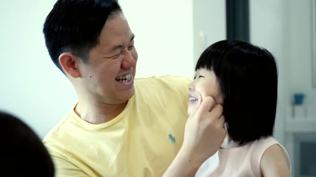 Loving dad is playful with his adorable preschool age daughter Mid adult Asian father smiles while pinching his daughter's cheek. They both are laughing and smiling at one another. They then give eskimo kisses. pinching stock videos & royalty-free footage