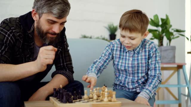 vídeos y material grabado en eventos de stock de padre amoroso es jugando al ajedrez con su hijo pequeño, enseñarle reglas y hablar con él. crianza de niños, juegos intelectuales y concepto de infancia feliz. - tablón