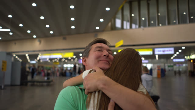 Loving daughter hugging her dad at the airport while he kisses her goodbye video