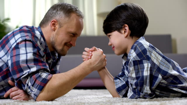 Loving father and kid arm wrestling on the floor, weekend leisure at home, fun video