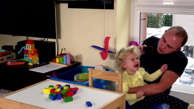 愛情のある父ブラシ自宅で彼女の娘少女の髪をとかす ビデオ