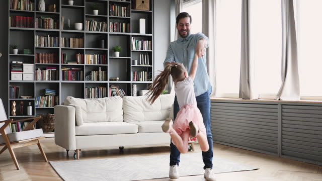 Loving father having fun spinning with child daughter at home Loving father having fun spinning dancing with cute little child daughter princess wear crown in modern living room, happy dad and small kid girl playing enjoying funny active dance together at home father stock videos & royalty-free footage