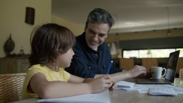 loving father helping his son with homework while working on laptop and enjoying a coffee - praca domowa filmów i materiałów b-roll